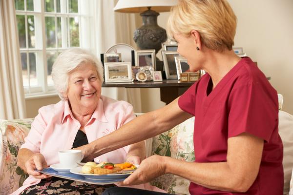 Carer serving meal to older lady