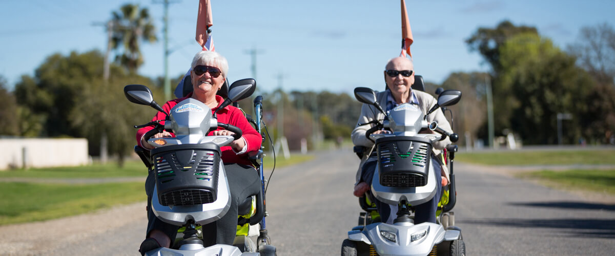 A couple of older people who are wearing sunglasses whilst riding along on mobility scooters. One is a woman and the other is a man, both have grey hair.