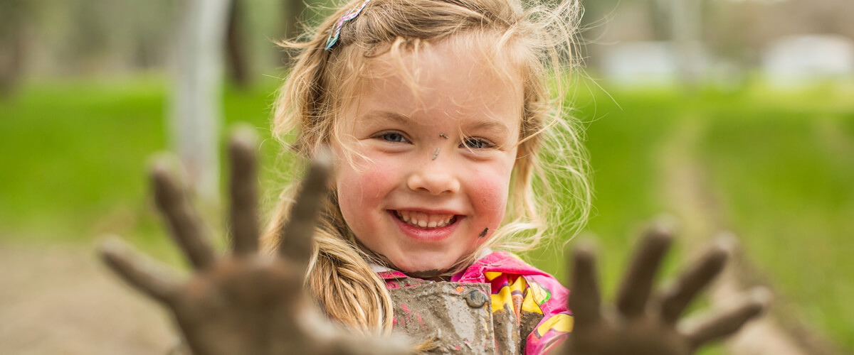 A little girl covered in brown mud smiling whilst facing the camera, proudly showing off a pair of very muddy hands.