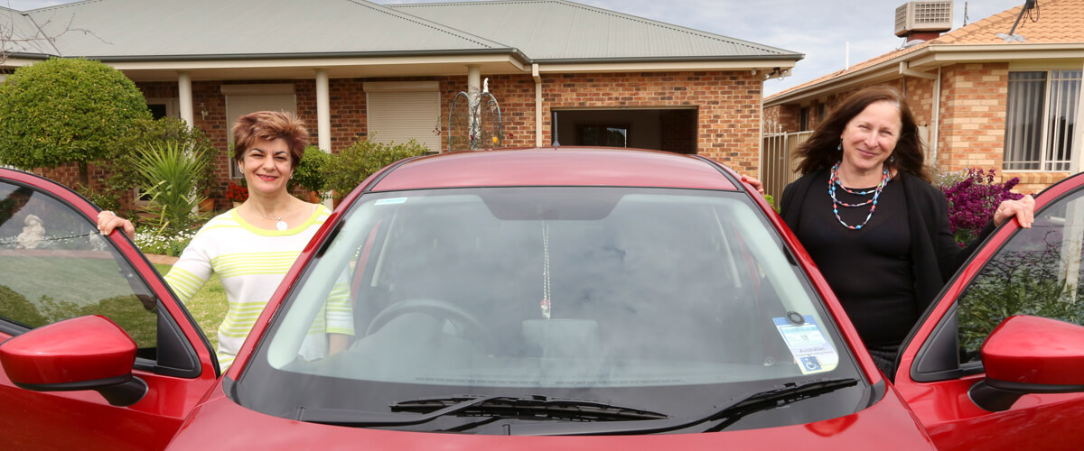 A cropped photo of Ability Links, Linker Simone and another woman standing on either side of a red car with the doors open.