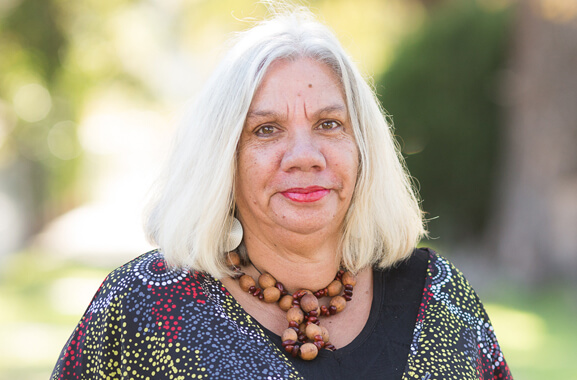A first Australian Aboriginal woman, with shoulder length grey hair, dressed in a shirt designed with Aboriginal artwork.