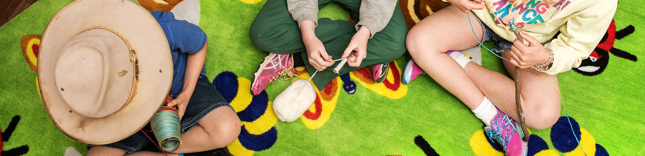 A cropped image of three children sitting on a colorful mat playing with balls of wool wrapping it around objects. The image is presented from directly above the children.