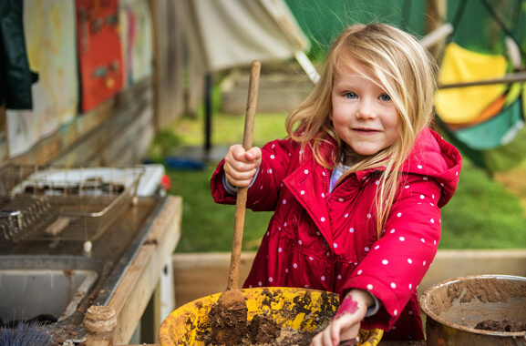 A little girl who is wearing a long red coat with small white polka dots. She is mixing dirt and water with a large wooden spoon in a yellow colored bowl.