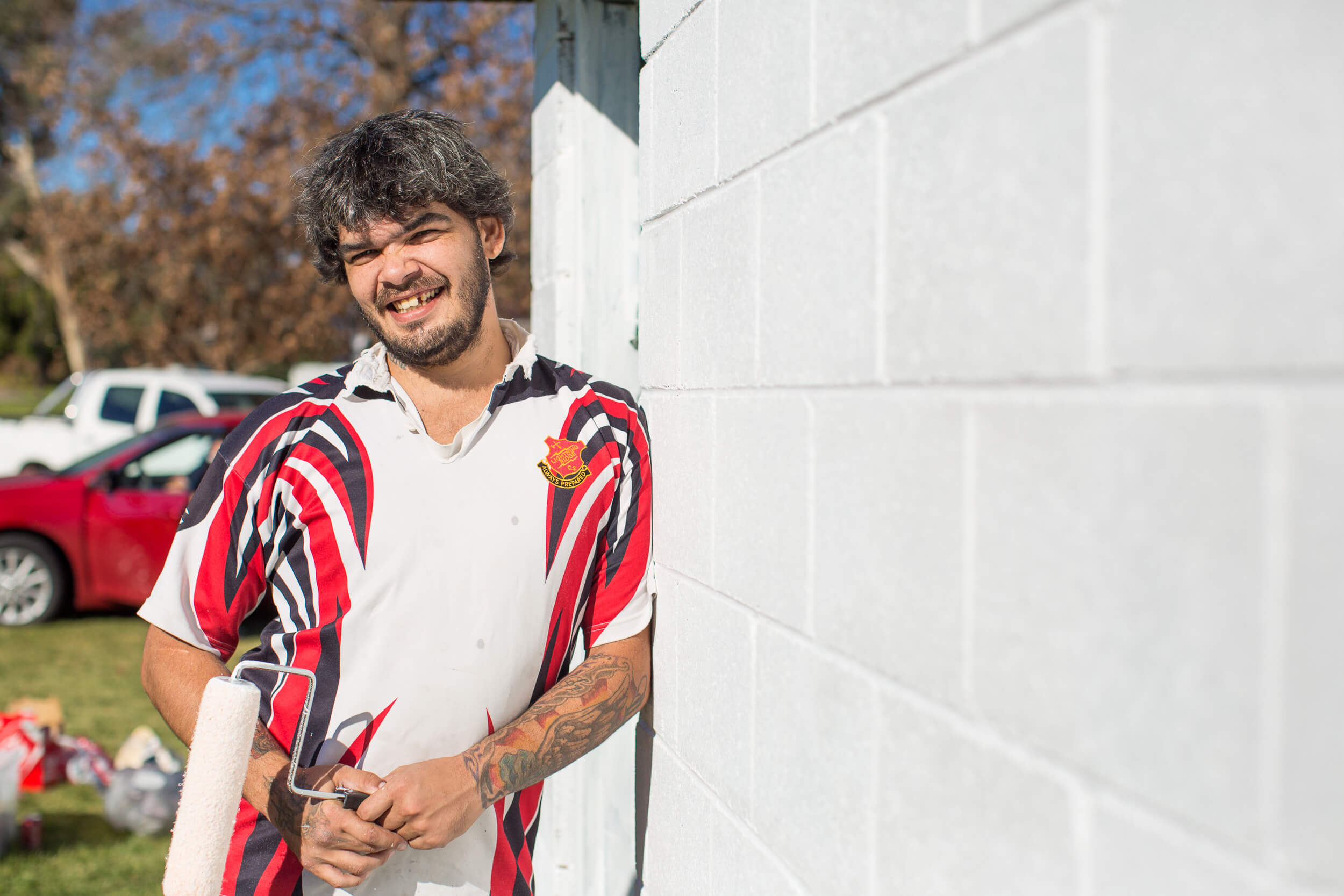 A first Australian Aboriginal man standing and grinning towards the camera. He has black and gray hair. He is wearing a red, white and black Rugby union jumper. He is standing beside a white cinderblock building with two cars, colored red and white, in the background. The skyscape features deciduous trees whose leaves are turning brown.