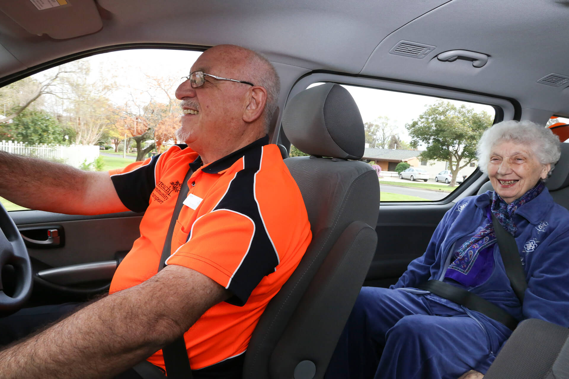 A Community Transport Driver sits in the driver's seat of a vehicle with an older woman in the driver side rear passengers seat