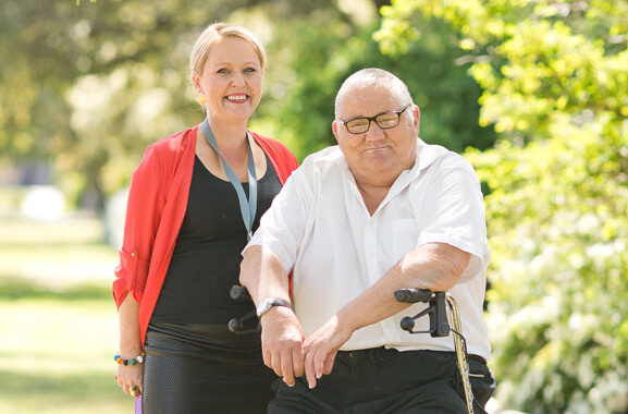 A woman and a man smiling to the camera. The woman has blonde hair which is tied back on to her head. She is wearing a black shirt and pants and the shirt is covered with a red cardigan. The man is sitting on the seat of his walking frame. His walking frame is a piece of equipment which provides additional support to an individual when walking or standing. He has greying hair which is cut short. He is dressed in black pants and a white button up shirt. There are green leafy shrubs in the background.