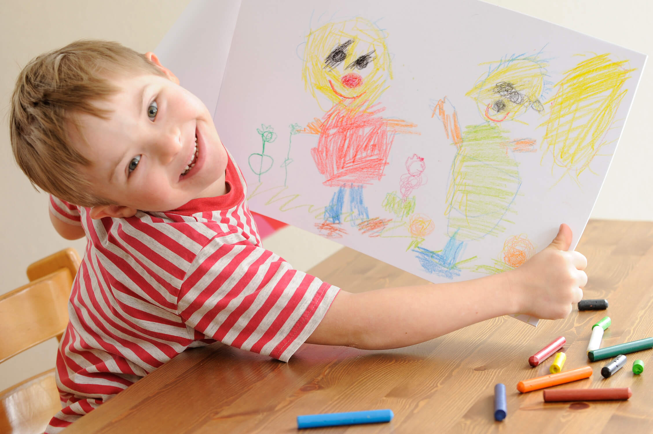 A cropped image taken of a young boy from above who is smiling up to the camera. He is holding a coloured drawing he has done.