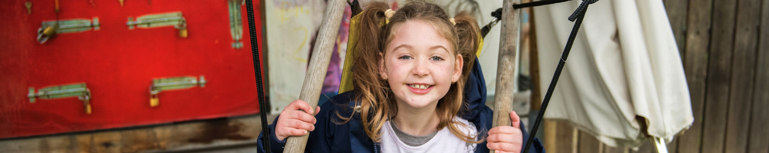 A cropped image of a young girl smiling to the camera whilst sitting in a timber and canvas seat.