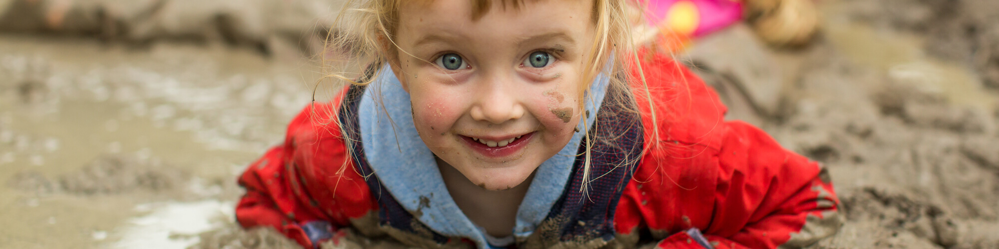 A young girl looking at the camera smiling whilst lying on her front in the mud.
