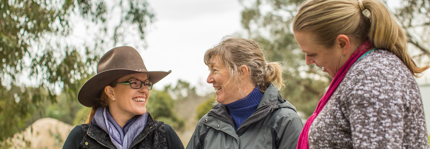 Three smiling woman standing whilst having a talk. One woman is with mouse brown hair is wearing an Akubra hat, one has mouse brown greying hair, one woman has blonde hair
