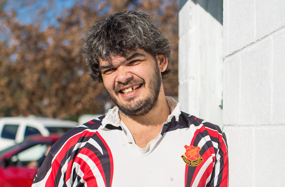 A first Australian Aboriginal man standing and grinning towards the camera. He has black and gray hair. He is wearing a red, white and black Rugby union jumper. He is standing beside a white cinderblock building with two cars, coloured red and white, in the background. The skyscape features deciduous trees whose leaves are turning brown.