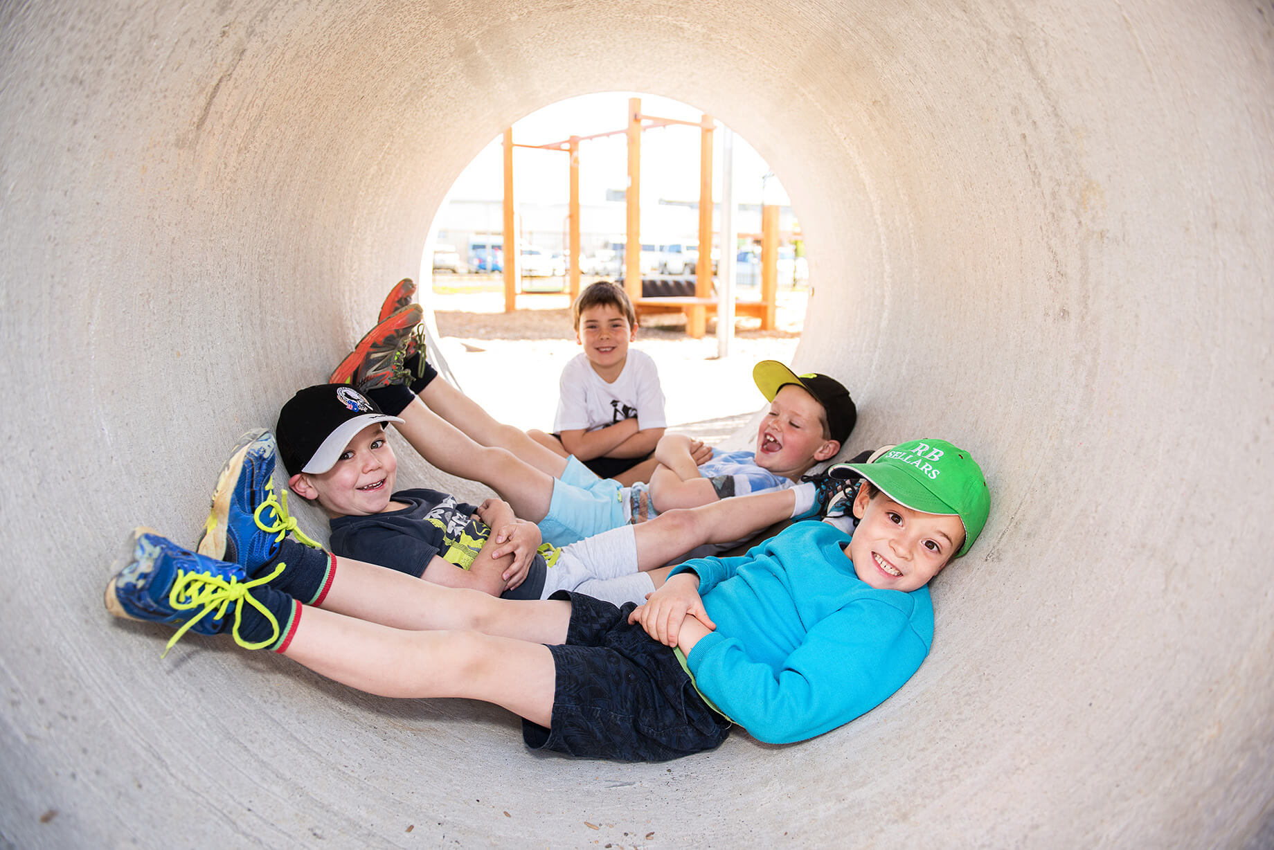 Four young boys are in a concreate pipe, three of them are laying across the pipe and one is sitting at the end of the pipe.