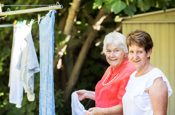 Corner of a 'Hills Hoist' clotheslines with three items of clothes hanging to dry on it. Two women are standing underneath and to the corner of the clothesline, One of the woman is about to hang another item of clothing on it. A large tree full of leaves and corner of garden shed appear in the background.