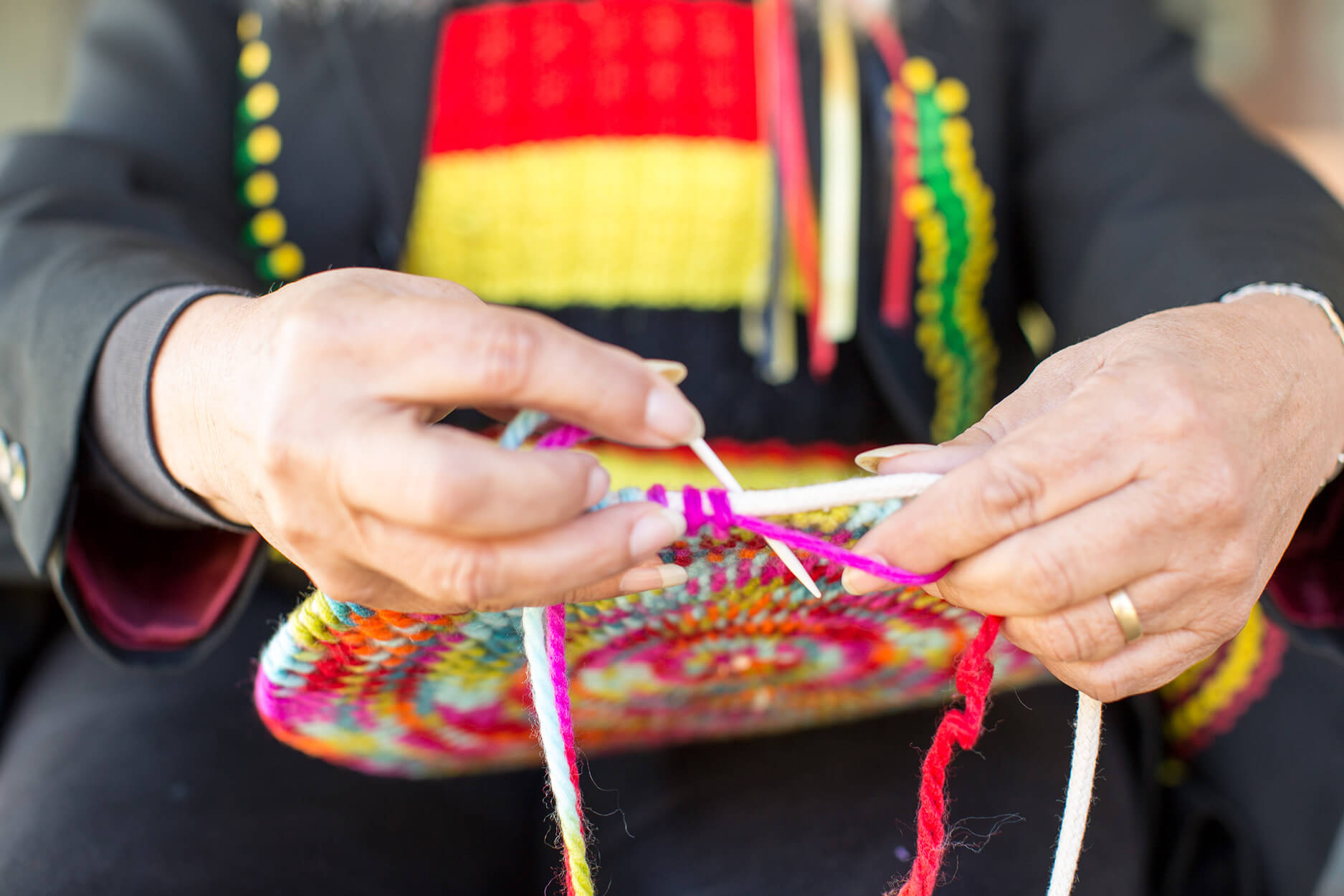 A image of a feminine hands knitting with one knitting needle and colorful wool