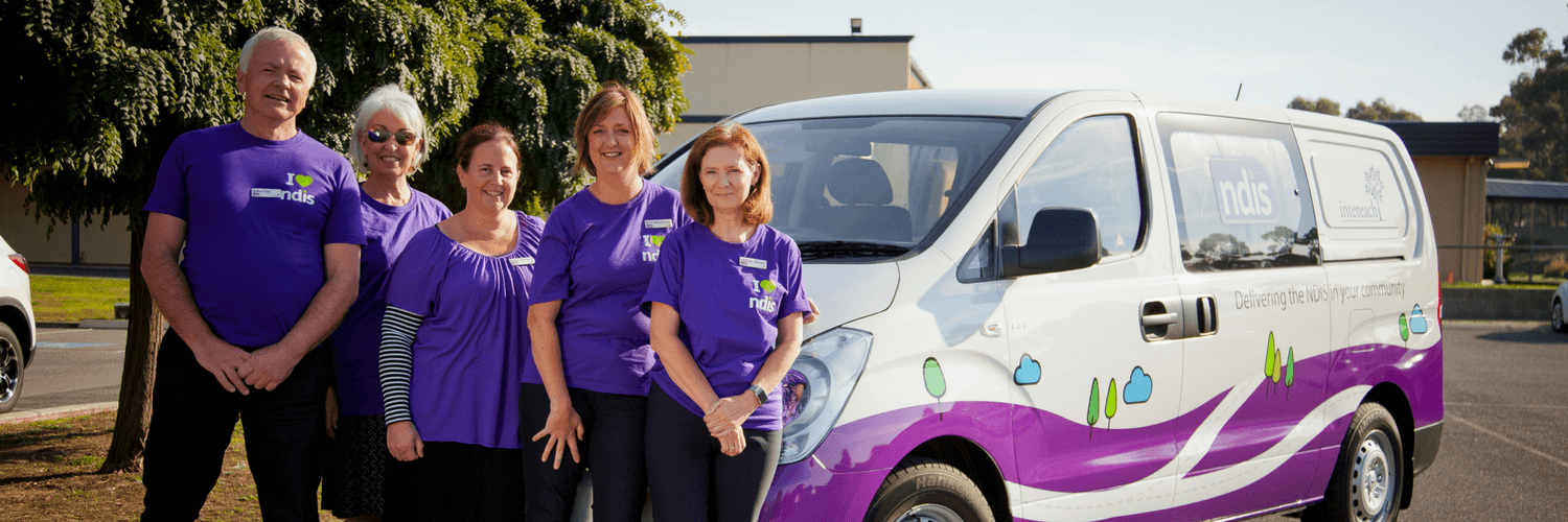 A full photo showing five Intereach employees standing in front of 'IVAN', the Intereach, National Disability Insurance Scheme (NDIS) Loddon Information van. All employees are wearing NDIS corporate tee-shirts which are purple.