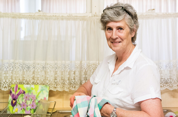A woman who is standing in front of a kitchen sink. The sink is framed by a window in the background. The window has lace hanging curtains. She is drying a piece of crockery with a pink, green and white colored cloth tea-towel. This woman is a carer of older people and or people with a disability