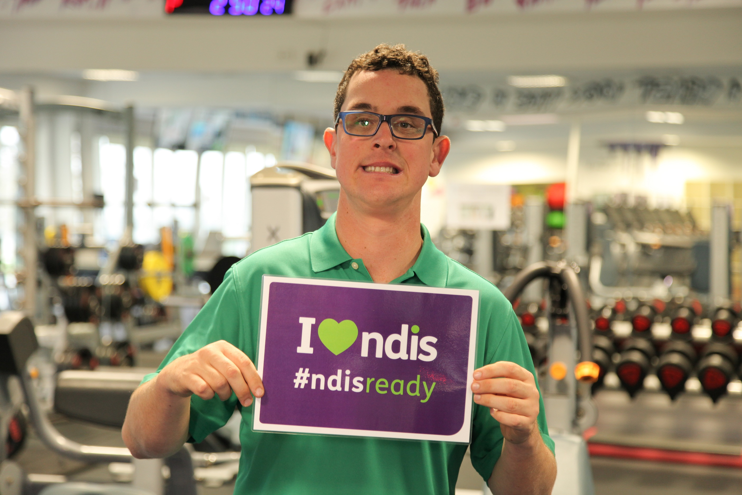 Man holding up 'I love NDIS #NDISready' sign