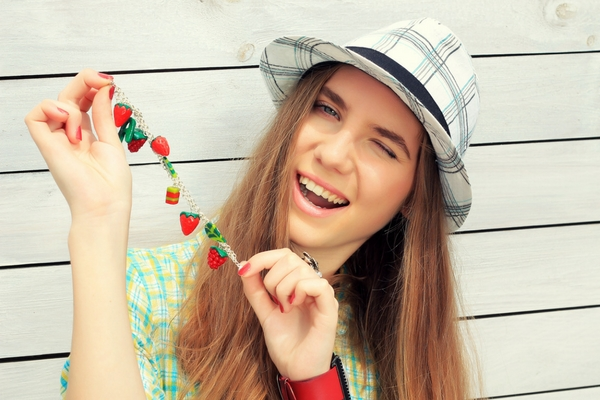 Young woman wearning a hat and holding a charm bracelet with sberry shaped charms