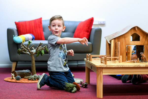 Child plays with toys in Intereach family room