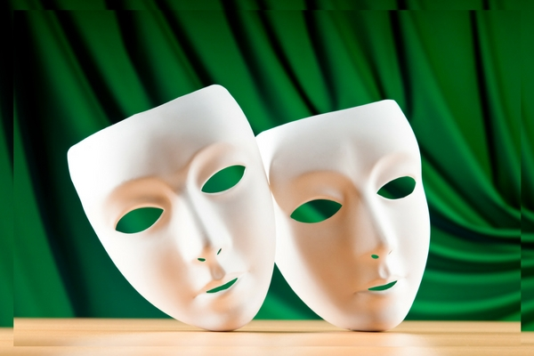 Two white theatre masks against the background of a green theatre curtain