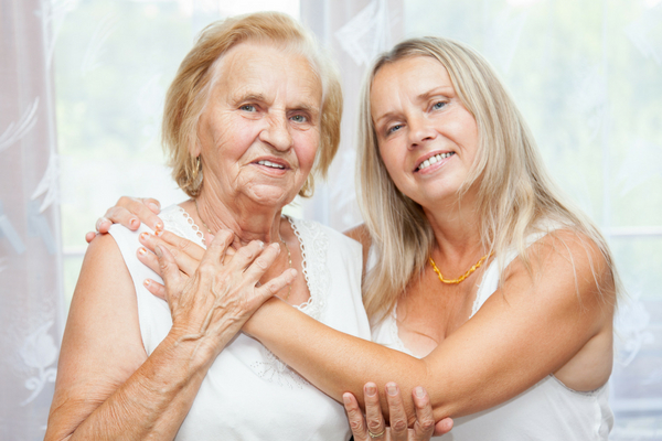 An older woman being embraced by her daughter