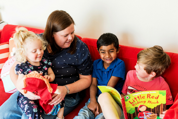 Family day care educator reads a book with three young children