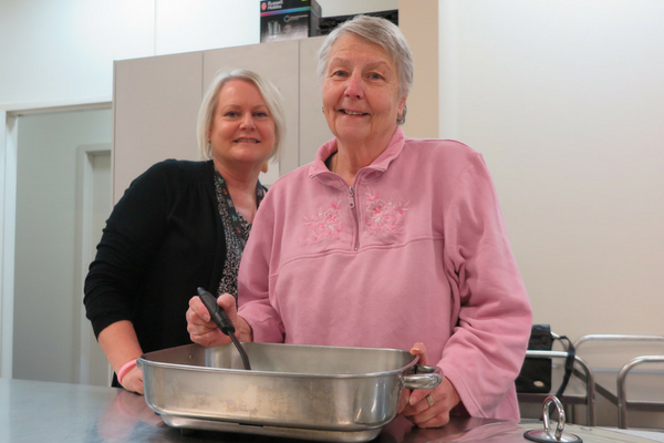 Two women cooking with a large silver pan