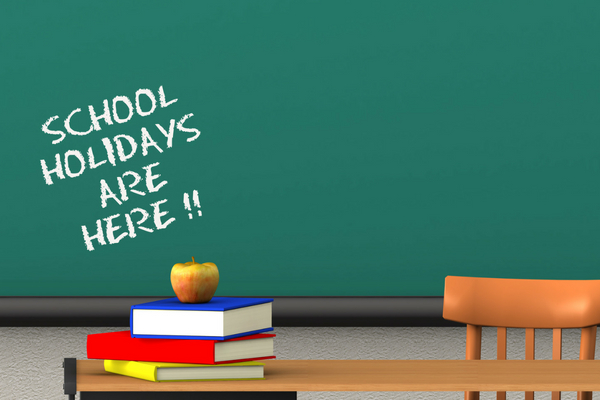"""Chalkboard reading """"School Holidays are here!!!"""" with a pile of books and an apple in front"""