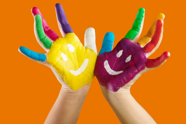 Child's hands covered with paint with a smiley face painted on