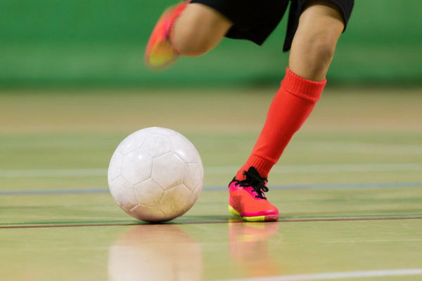Legs clad in red socks and shoes kicking a soccer ball