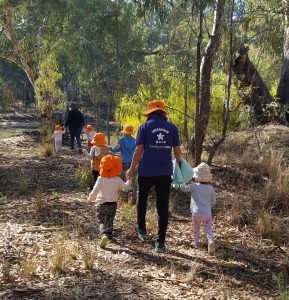 Family Day Care worker walking with children in bush