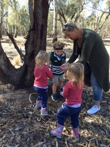 Lady showing children some bugs