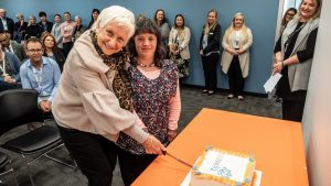 Intereach chair Pat Fogarty and NDIS participant Nadia cutting a cake