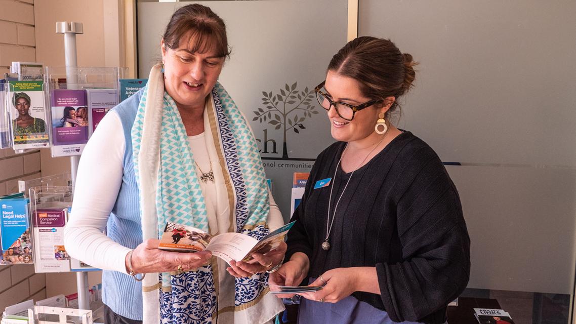 Woman reading brochure next to Intereach staff member