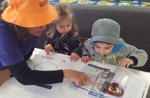 Family Day Care worker showing magazine to two children