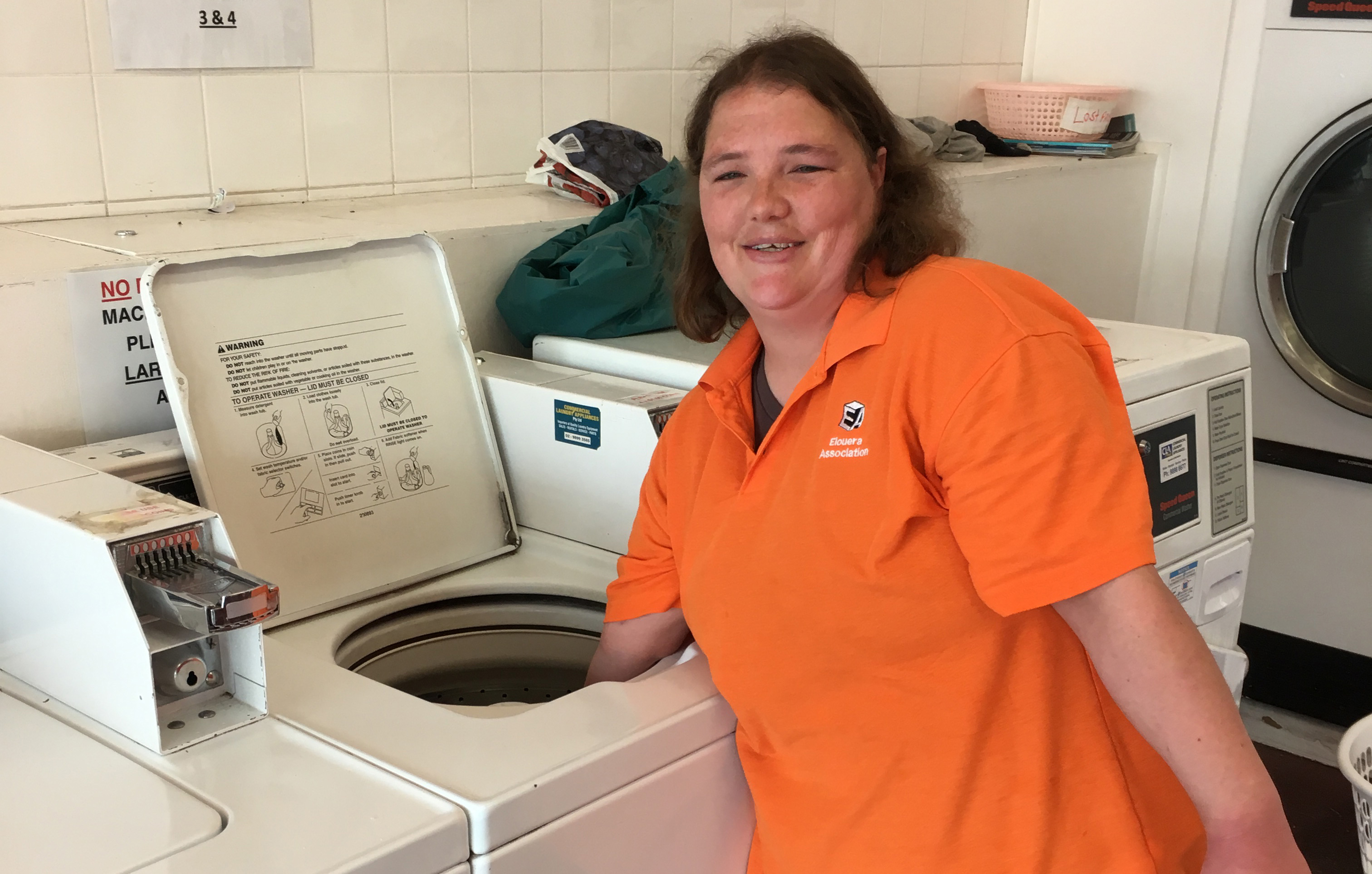 Woman Tarah Ross reaching into washing machine